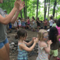 As we wait for all campers to join our big circle, we have some fun in a conga line